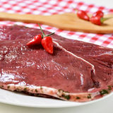Raw marinated beef fillets. Closeup of some raw marinated beef fillets on a plate on the kitchen table ready to be cooked Stock Photo