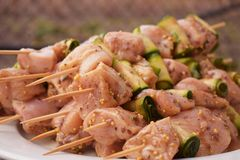 Raw Marinated Chicken Meat Skewers. Barbeque Summer Picnic Food. Grilled Meat over Wooden Background with Spices. Grilled Chicken Skewers. Barbeque Summer Picnic Stock Images
