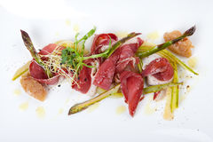 Raw marinated green asparagus with smoked duck breast Royalty Free Stock Photography