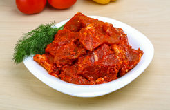 Raw marinated meat for bbq. With herbs and spices on red tomato sauce Royalty Free Stock Photo