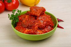 Raw marinated meat for bbq. With herbs and spices on red tomato sauce Royalty Free Stock Image