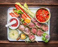 Raw marinated meat skewers with spices and vegetables for grill or roasting. On dark wooden background, top view Stock Photography