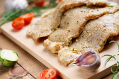 Raw marinated pork meat and vegetables. On wooden cutting board Royalty Free Stock Photography