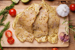 Raw marinated pork meat and vegetables. On wooden cutting board Royalty Free Stock Photo