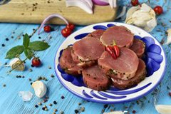 Raw marinated pork medallions. Some raw marinated pork medallions in a ceramic plate, placed on a blue rustic wooden table sprinkled with peppercorns and stock images