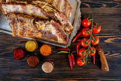 Raw marinated pork ribs and tomatoes of garlic pepper on a black board. Raw fresh meat and vegetable on wooden background Royalty Free Stock Images