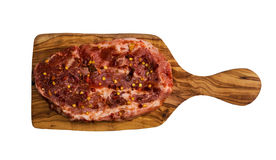 Raw marinated pork steak with red pepper flakes, on cutting board made from olive wood. Isolated on white background, top view.  Royalty Free Stock Photography