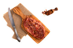 Raw marinated pork steak, red pepper flakes, vintage knife isolated on white background. Top view.  Royalty Free Stock Photography