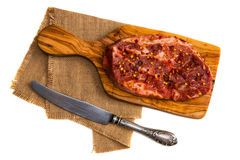Raw marinated pork steak, red pepper flakes, vintage knife isolated on white background. Top view.  Royalty Free Stock Images