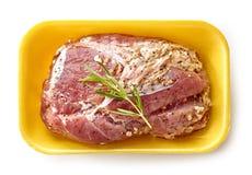 Raw marinated pork tenderloin in plastic try Stock Photo