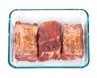 Raw marinated ribs. In glass tray separated on white background Royalty Free Stock Photos
