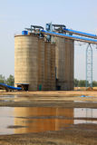 Raw material warehouse and a conveyor belt in a cement factory Stock Photo