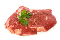 Raw matured rib eye with spices and coriander. Against white background Royalty Free Stock Photos