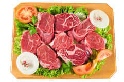 Raw meat. Slices of raw meat with vegetables on a cutting board Stock Image