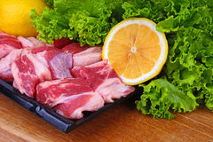 Raw Meat. Uncooked cow meat on plate with lemon and lettuce royalty free stock images