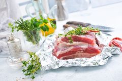 Raw meat in foil. Raw meat with aroma spice and salt, stock photo Stock Image