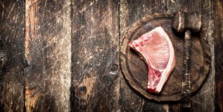 Raw meat background. Raw piece of pork with a wooden hammer on a cutting Board. On the old wooden table Royalty Free Stock Photos