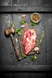 Raw meat background. Raw piece of steak with rosemary and spices. Royalty Free Stock Image