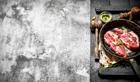 Raw meat background. Raw pork chop in an old pan with spices and herbs. Royalty Free Stock Photo