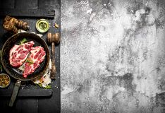 Raw meat background. Raw pork chop in an old pan with spices and herbs. Stock Images