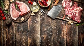 Raw meat background. Raw pork chop with a variety of herbs and spices. Royalty Free Stock Photo