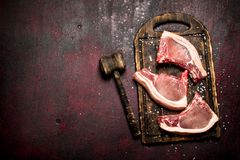 Raw meat background. Raw pork is with the old hammer. On rustic metal background Stock Photography