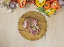 Raw meat on a background of vegetables and greens, on a wooden board. Top view, colorful composition Stock Images