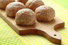 Raw meat balls. Six beef balls from minced meat laid on wooden cutting board Stock Photography