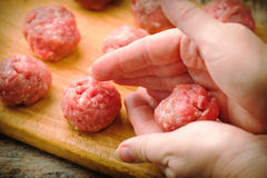 Raw meat balls on a chopping board. Royalty Free Stock Photography