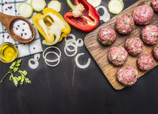 Raw meat balls with herbs and onions on a cutting board with bell peppers, butter,  on wooden rustic background top view. Raw meat balls with herbs and onions on Stock Image