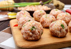 Raw meat balls, ready for cooking on a cutting board. Stock Images