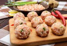 Raw meat balls, ready for cooking on a cutting board. Stock Photo