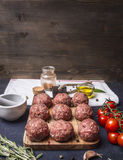 Raw meat balls vegetables, butter and herbs on wooden rustic background top view close up border,with text area. Raw meat balls with vegetables, butter and herbs Stock Photos