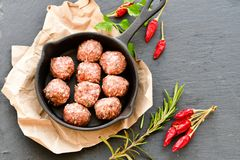Raw meat balls vintage cast-iron pan. With tomatoes, onions and peppers, herbs on wooden rustic background top view close up, black pepper , red chili peppers Royalty Free Stock Images