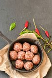 Raw meat balls vintage cast-iron pan. With tomatoes, onions and peppers, herbs on wooden rustic background top view close up, black pepper , red chili peppers Stock Image