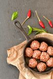 Raw meat balls vintage cast-iron pan. With tomatoes, onions and peppers, herbs on wooden rustic background top view close up, black pepper , red chili peppers Stock Images