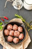 Raw meat balls vintage cast-iron pan. With tomatoes, onions and peppers, herbs on wooden rustic background top view close up, black pepper , red chili peppers Royalty Free Stock Photography