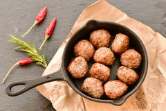 Raw meat balls vintage cast-iron pan. With tomatoes, onions and peppers, herbs on wooden rustic background top view close up, black pepper , red chili peppers Stock Photos