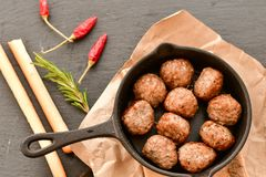 Raw meat balls vintage cast-iron pan. With tomatoes, onions and peppers, herbs on wooden rustic background top view close up, black pepper , red chili peppers Royalty Free Stock Photo