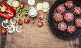 Raw meat balls in vintage cast-iron pan with tomatoes, onions and peppers, herbs on wooden rustic background top view close up. Raw meat balls vintage cast-iron Royalty Free Stock Photos