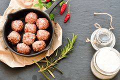 Raw meat balls vintage cast-iron pan. With tomatoes, onions and peppers, herbs on wooden rustic background top view close up, black pepper , red chili peppers Stock Photography