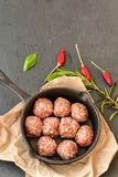 Raw meat balls vintage cast-iron pan. With tomatoes, onions and peppers, herbs on wooden rustic background top view close up, black pepper , red chili peppers Stock Photo