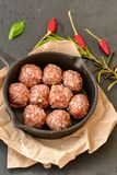 Raw meat balls vintage cast-iron pan. With tomatoes, onions and peppers, herbs on wooden rustic background top view close up, black pepper , red chili peppers Royalty Free Stock Photos