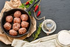 Raw meat balls vintage cast-iron pan. With tomatoes, onions and peppers, herbs on wooden rustic background top view close up, black pepper , red chili peppers Royalty Free Stock Image