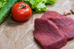 Raw meat barbecue with fresh vegetables wooden surface. Food, steak, beef bbq, tomatoes, peppers, spices for cooking. Stock Photos