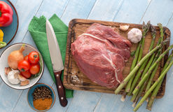 Raw meat beef on blue wooden table with different vegetables. Fresh raw meatbeef tenderloin on cutting board on blue wooden table with different vegetables. Top Stock Photography