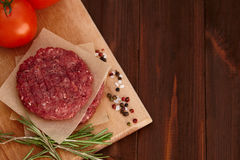 Raw meat beef burger with tomatoes and spices Royalty Free Stock Photography