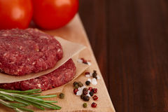 Raw meat beef burger with tomatoes and spices Royalty Free Stock Photos