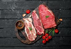 Raw meat. Beef and pork steaks with spices on the cutting Board stock images