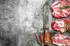 Raw meat of beef with rosemary and hot peppers. On rustic background Stock Images